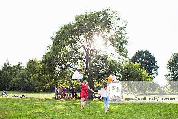 Rückansicht von zwei jungen Frauen  die mit Luftballons auf der Parkparty tanzen.