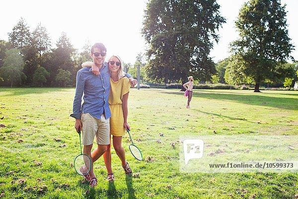 Romantisches junges Paar mit Badmintonschlägern im sonnigen Park