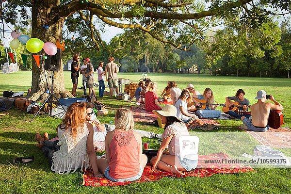 Gruppe von Freunden  die Musik unter dem Parkbaum bei Sonnenuntergang hören.