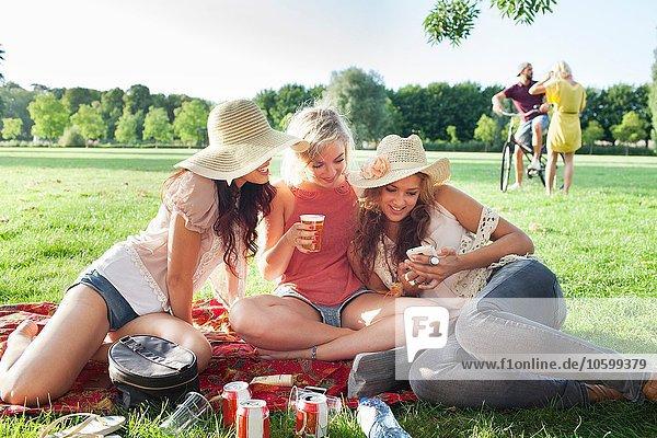 Freundinnen lesen Smartphone-Text auf der Parkparty