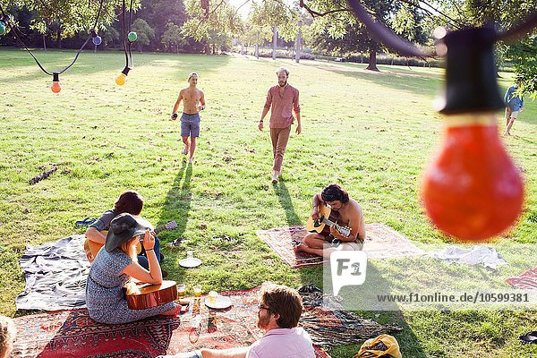 Blick auf erwachsene Partygäste  die bei Sonnenuntergang Gitarre spielen.
