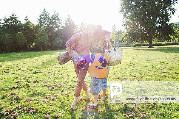 Romantisches junges Paar mit Teppich im Park