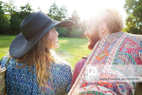 Rückansicht des romantischen jungen Paares mit Teppich zum Picknick im Park