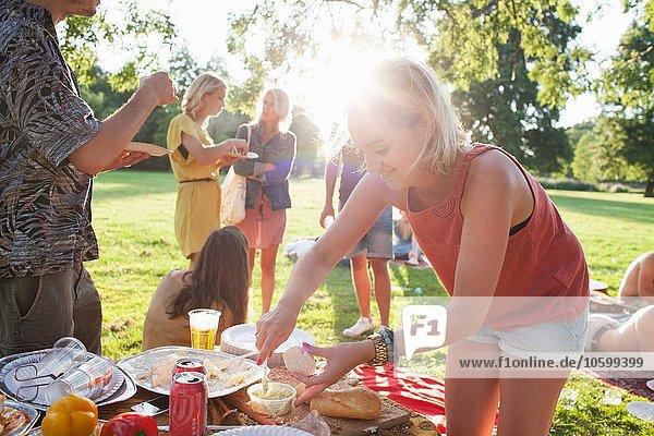 Junge Frau beim Picknick in der Gruppe im Park