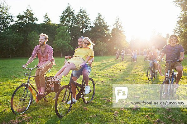 Massen von Erwachsenen  die mit dem Fahrrad zum Sonnenuntergang anreisen.