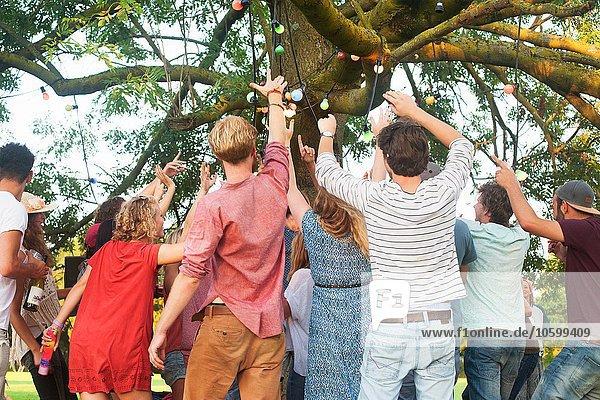 Rückansicht der erwachsenen Freunde beim Jubeln und Tanzen auf der Parkparty