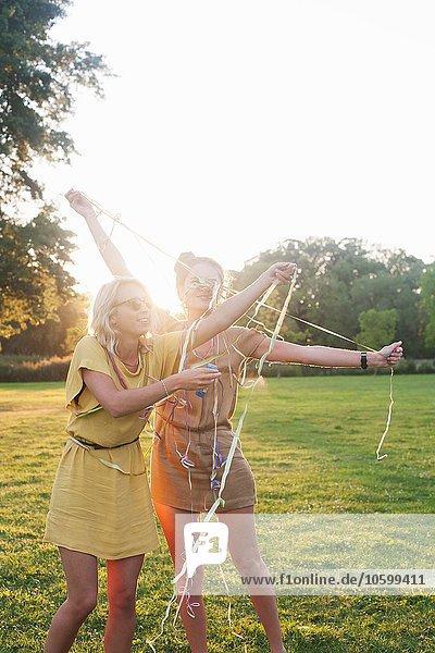 Zwei junge Frauenfreunde  die sich auf der Party im Park in Luftschlangen wickeln