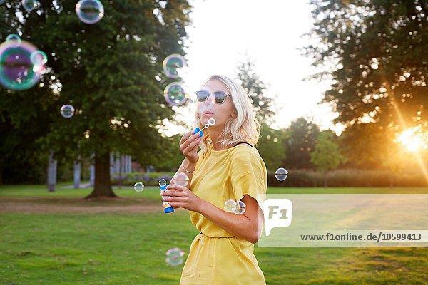 Porträt einer jungen Frau in gelbem Kleid  die bei Sonnenuntergang im Park Blasen bläst.