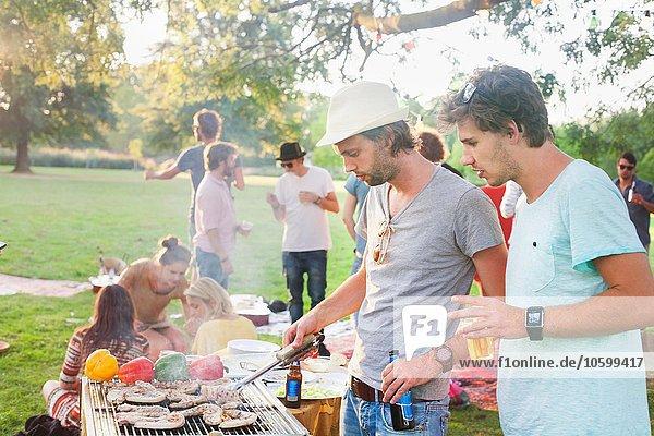 Junge Männer beim Grillen auf der Gruppenparty im Park