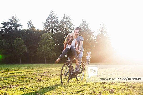 Junge Frau am Lenker von Freunden Fahrrad auf der Party im Park