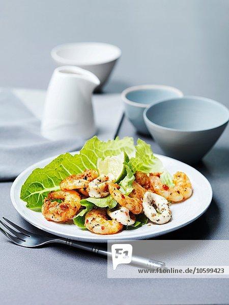 Tandoori-Garnelen und gegrillte Calamari mit Limettenscheibe und Kopfsalat