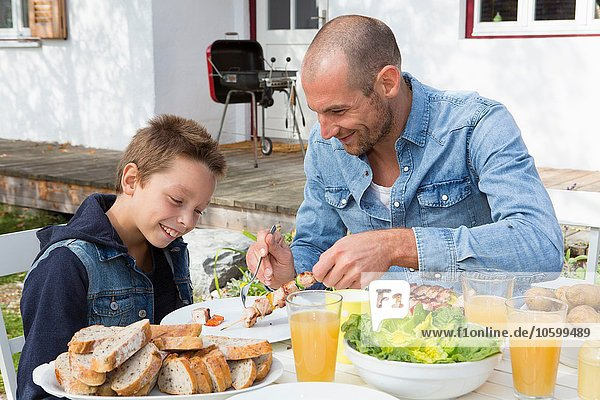 Father and son at garden barbecue table