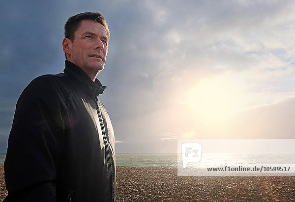 Portrait of mature man looking away from sunlit shingle beach
