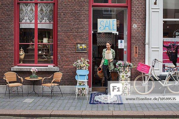 Junge Kundin mit Krug und Lampe vor dem Vintage-Shop