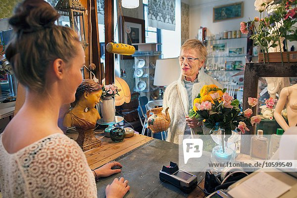 Mature female customer buying teapot in vintage shop