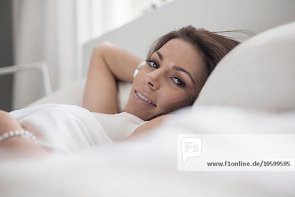 Junge Frau auf dem Bett liegend
