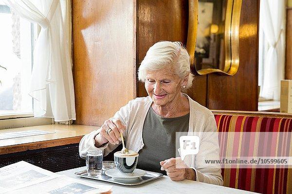 Seniorin im Café sitzend  Kaffee rührend