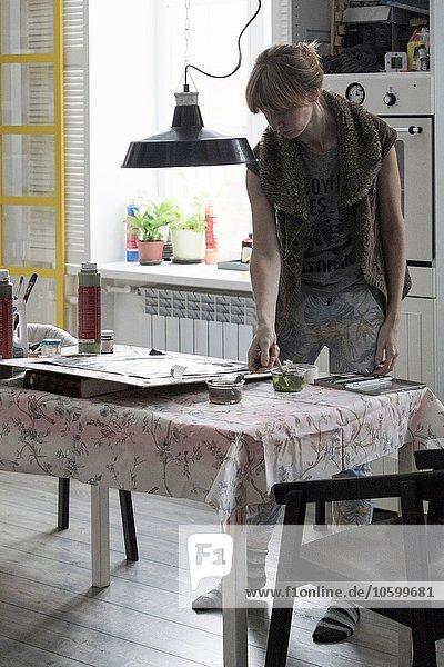 Künstlerin bei der Arbeit am Küchentisch