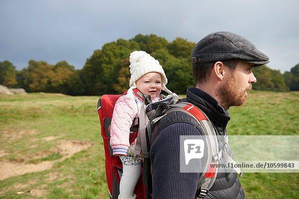 Seitenansicht eines erwachsenen Mannes im Feld mit flacher Mütze und Tochter auf dem Rücken im Tragesitz.