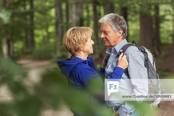 Couple standing face to face in forest