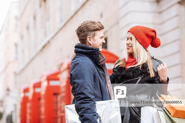 Young shopping couple and red phone boxes  London  UK