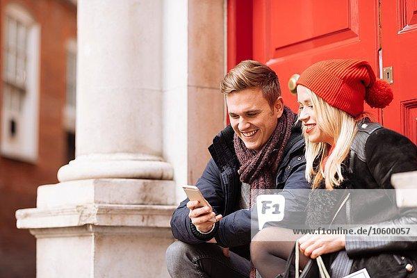 Junges Paar beim Lesen von Smartphone-Texten vor der Haustür  London  UK Junges Paar beim Lesen von Smartphone-Texten vor der Haustür, London, UK