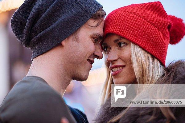 Kopf- und Schulteraufnahme eines romantischen jungen Paares mit Strickmützen Kopf- und Schulteraufnahme eines romantischen jungen Paares mit Strickmützen