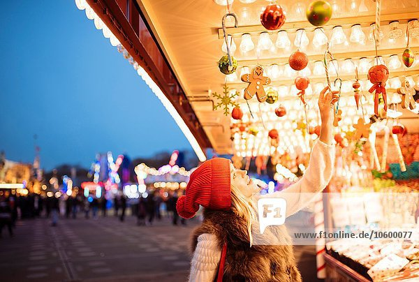 Young woman choosing baubles at xmas festival in Hyde Park  London  UK