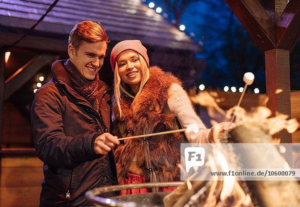 Young couple toasting marshmallows at xmas festival in Hyde Park  London  UK