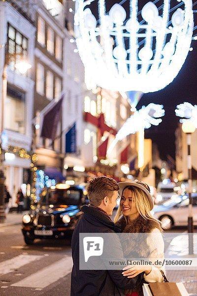 Romantic young couple on New Bond street at xmas  London  UK