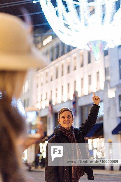 Junges Paar zeigt auf Weihnachtsbeleuchtung in der New Bond Street  London  UK Junges Paar zeigt auf Weihnachtsbeleuchtung in der New Bond Street, London, UK