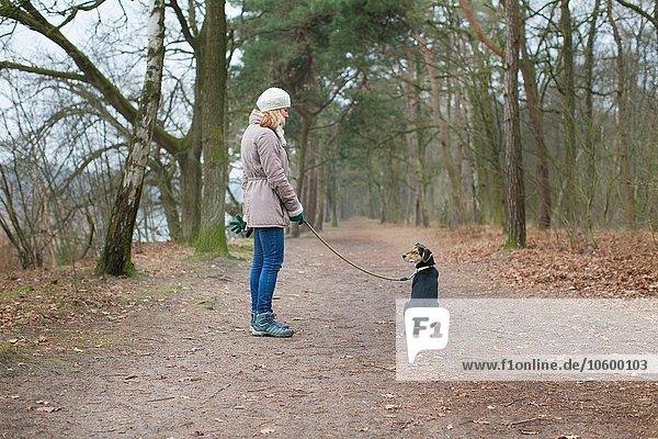 Mittlere erwachsene Frau und ihr Hund im Wald