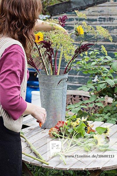 Abgeschnittene Ansicht einer reifen Frau  die bei der Zuteilung frische Blumen arrangiert.