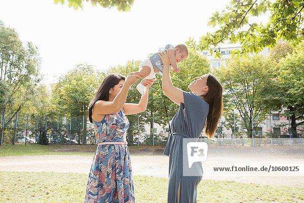 Junge Frau und Mutter halten das kleine Mädchen im Park hoch.