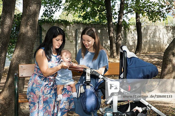 Junge Frau mit Mutter und Tochter auf Parkbank sitzend