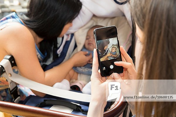 Young woman photographing mother and baby daughter on smartphone