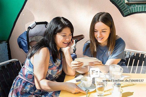 Junge Frau mit Mutter und Tochter beim Betrachten von Fotos im Straßencafé