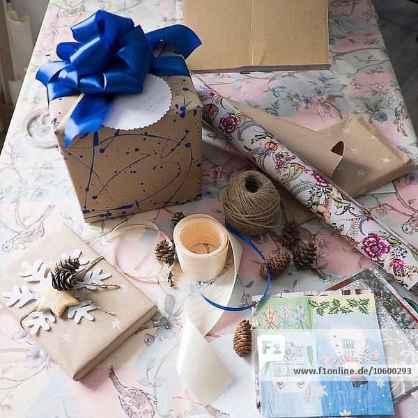 Hochwinkelansicht der Geschenkverpackung und Geschenk mit blauer Schleife auf dem Tisch