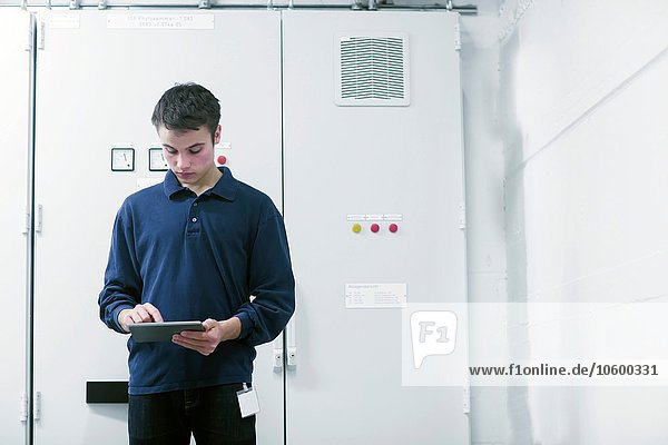 Front view of young man in switchgear control room using digital tablet looking down