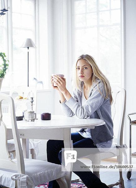 sitzend junge Frau junge Frauen Tasse halten Kaffee Tisch