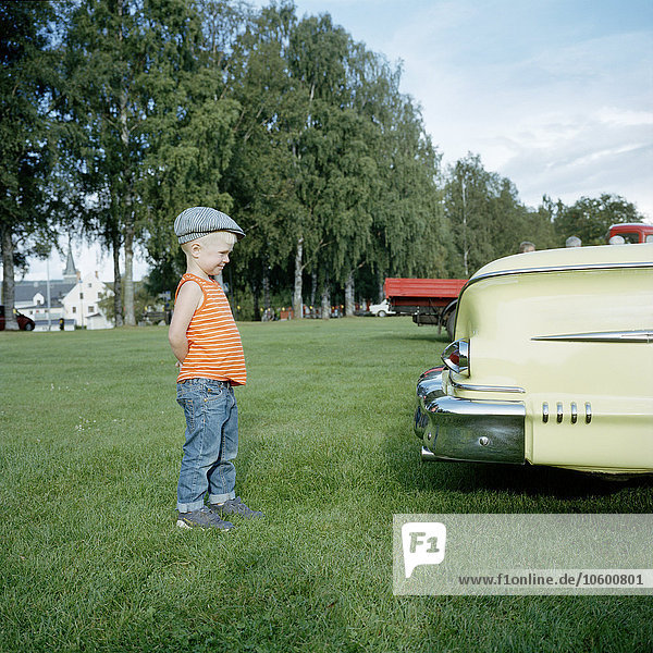Boy looking at vintage car