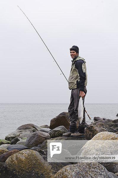 stehend Fisch Pisces Mann lächeln Küste halten angeln Stange