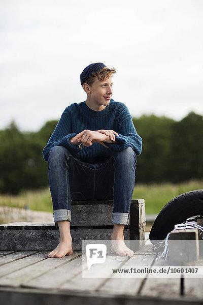 sitzend Jugendlicher sehen lächeln Junge - Person Steg wegsehen Reise