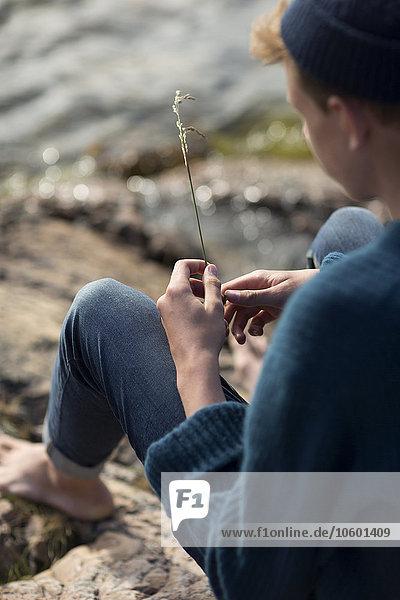 sitzend Jugendlicher Junge - Person halten Gras