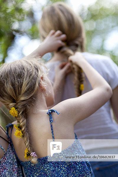 Girls braiding dandelion flowers