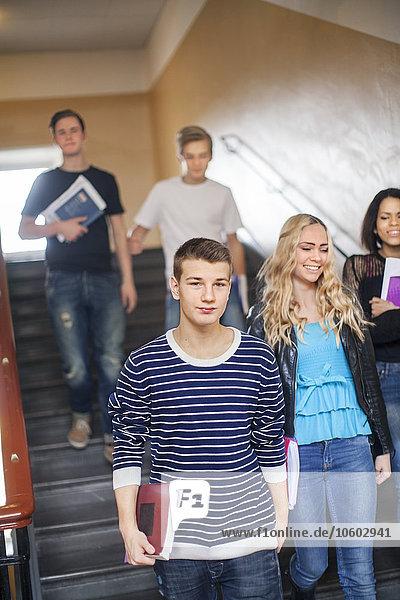 Teenage friends walking down stairs