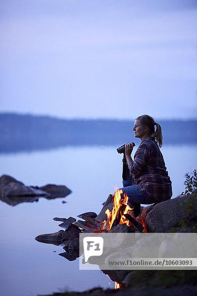 Lagerfeuer nahe sitzend Frau