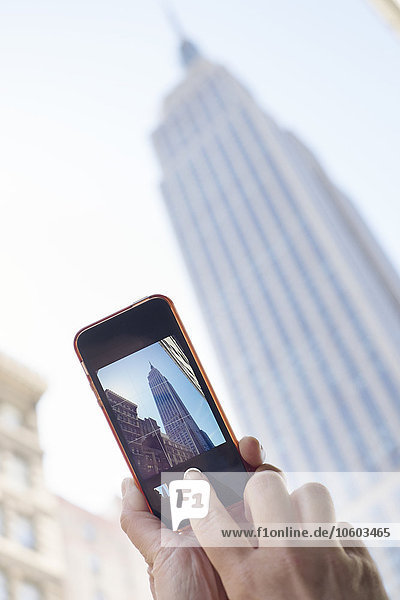 Woman taking picture of skyscraper with cell phone