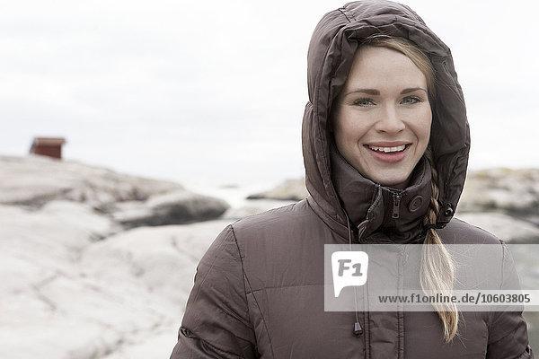 Smiling woman on rocky coast