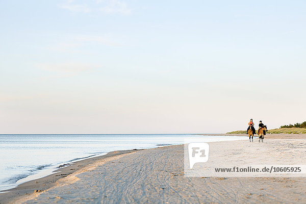 Two women horseback riding on beach
